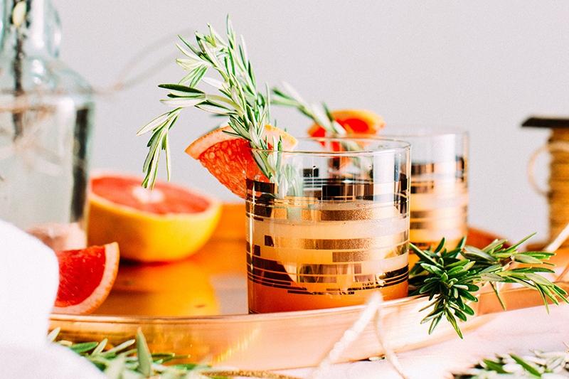 Flotte orange drinks på bakke med pynt.